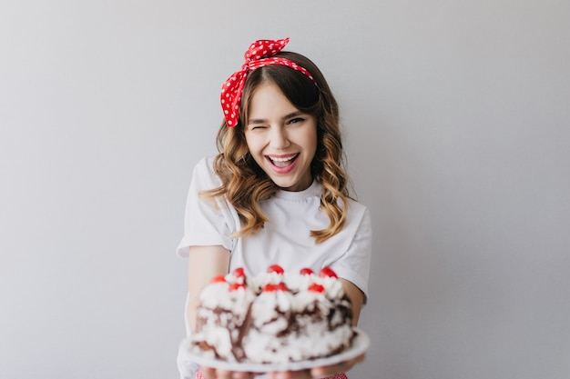 Debonair girl with romantic hairstyle posing with birthday cake. amazing laughing lady holding strawberry pie.
