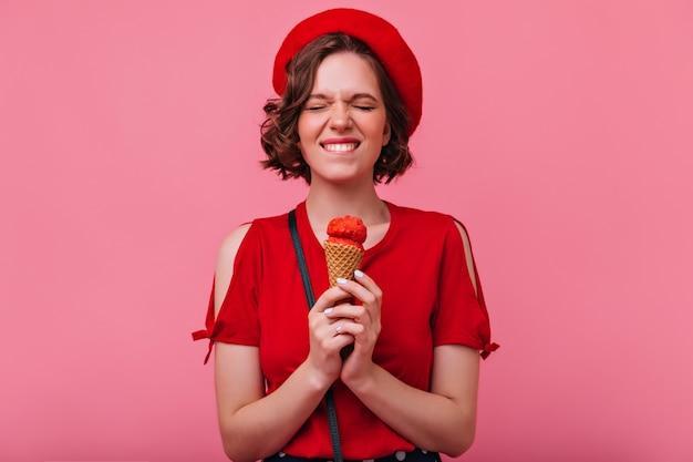 기쁨과 함께 아이스크림을 먹는 짧은 머리를 가진 debonair 소녀. 서 빨간 옷에 쾌활 한 백인 여자의 실내 사진.