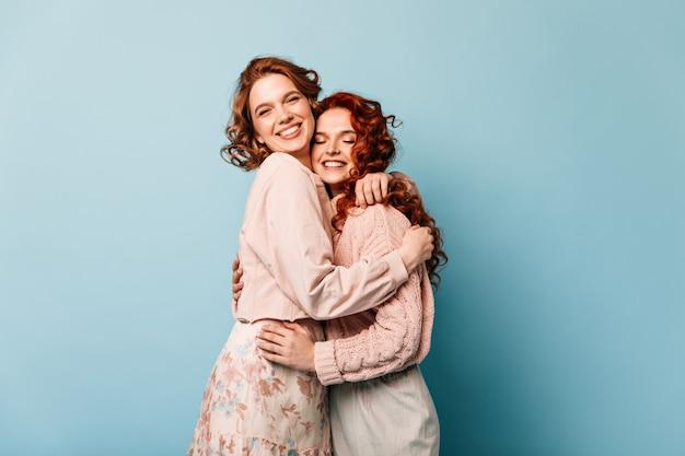 Ragazze debonair che si abbracciano su sfondo blu. studio shot di attraenti amici ridendo a porte chiuse.