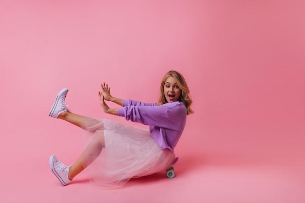 Debonair lady in trendy skirt sitting on skateboard. indoor portrait of positive carefree woman with blonde hair.