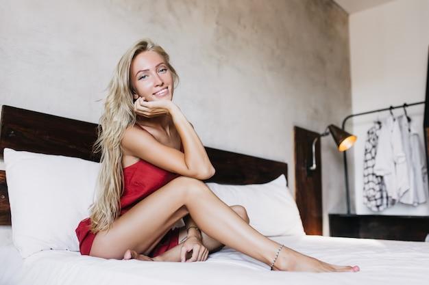 Debonair 가볍게 무두질 한 여자는 부드럽게 미소를 지으며 침대에 앉아 있습니다. 잠옷에 포즈를 취하는 스트레이트 머리를 가진 관심있는 유럽 여자.