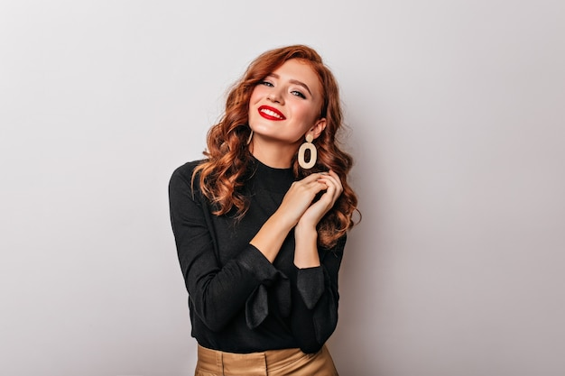 Debonair stylish woman in black blouse smiling.  graceful european girl wears golden earrings.
