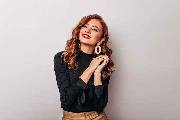 黒のブラウスの笑顔でデボネアスタイリッシュな女性。優雅なヨーロッパの女の子は金色のイヤリングを着ています。