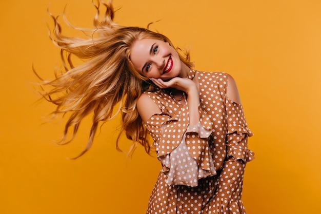 彼女の髪を振っているdebonairスタイリッシュな女性。壮観な女性モデルの室内写真は茶色の服を着ています。