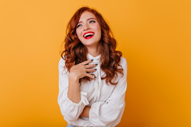 Debonair woman with wavy hairstyle laughing on yellow wall. indoor photo of graceful ginger lady in white blouse.