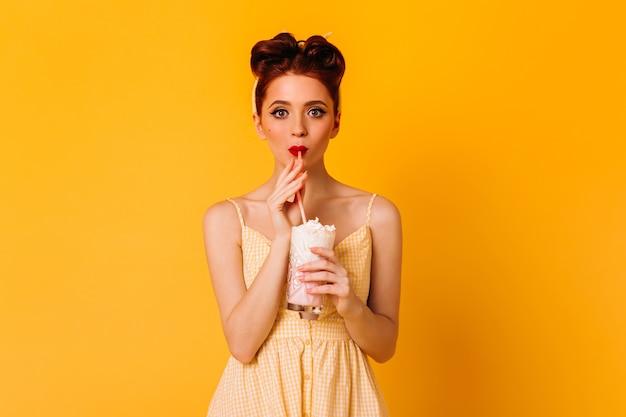 Debonair giovane donna che beve milkshake. bella ragazza dai capelli rossi in abbigliamento pinup in piedi sullo spazio giallo.
