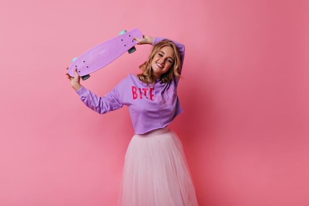 Debonair giovane donna in gonna lussureggiante agghiacciante. graziosa ragazza bionda con skateboard rosa.