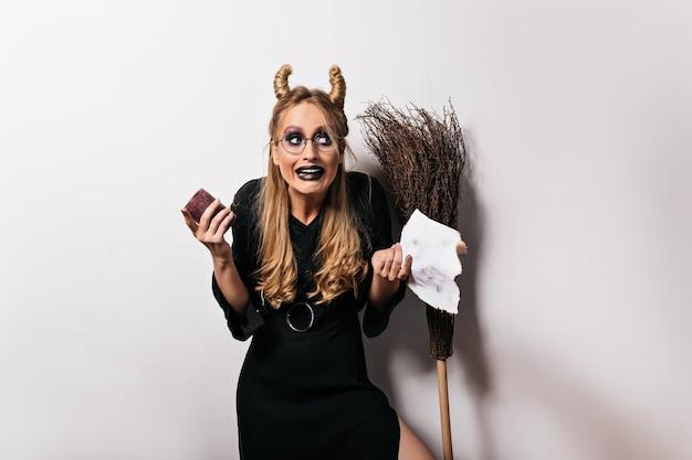 Debonair 젊은 뱀파이어 검은 드레스에 포즈. 흰 벽에 서있는 안경에 금발 세련 된 마녀.