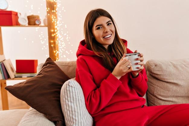 朝コーヒーを飲むデボネアの若い女性。ティーカップと幸せな女の子の屋内ショット。