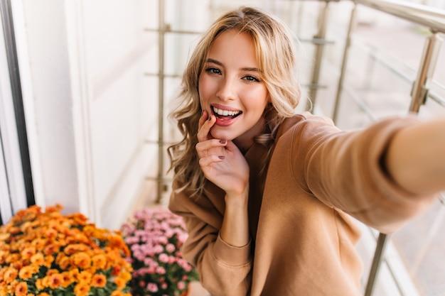Debonair 젊은 여자 발코니에서 셀카 만들기. 오렌지 꽃 옆에 포즈 웃는 꿈꾸는 소녀의 초상화.