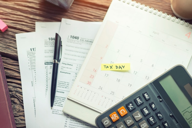 Debt collection and tax day with deadline calendar reminder note tax form 1040 with calculator.