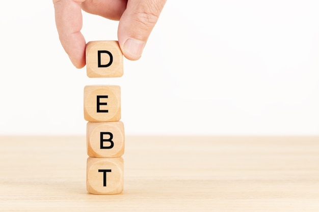 Debt concept. hand holding a pile of wooden blocks on table.