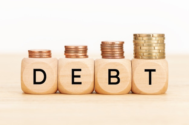 Debt concept. wooden blocks with text and coins on wooden table. copy space