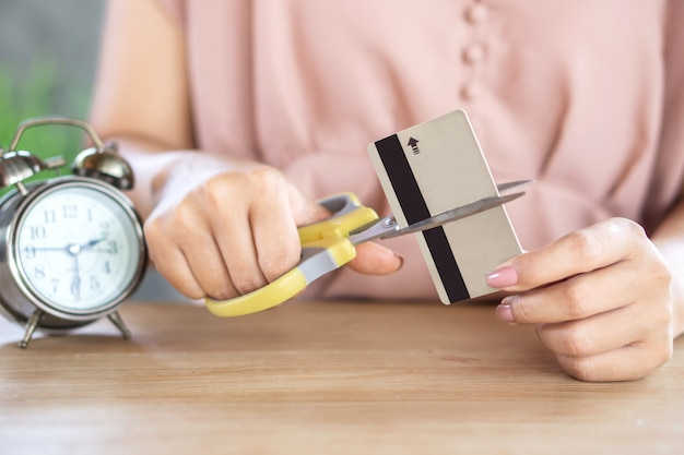 Debt free concept with woman hand cutting credit card