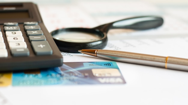 Debt free from credit card concept background with calculator and magnifier on desk, close up, business concept