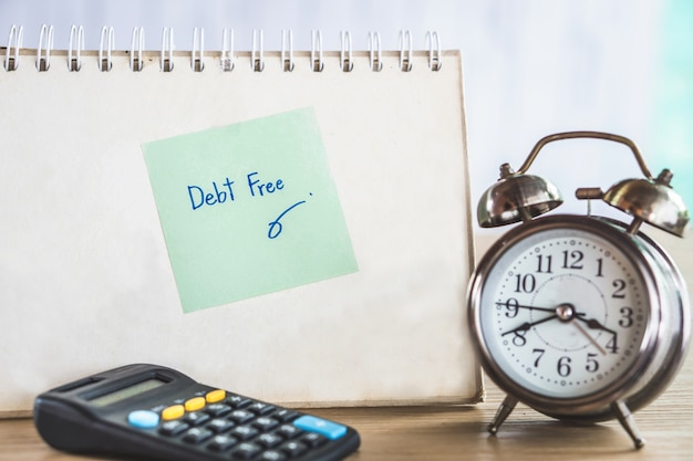 Debt free with clock and calculator on desk
