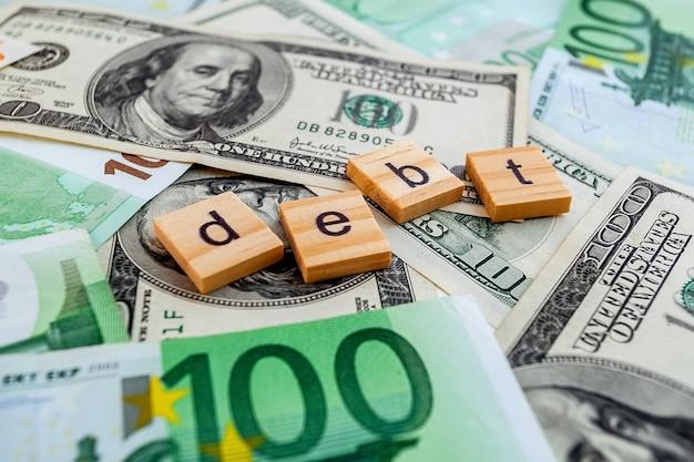 米ドルとユーロ紙幣の質感の木製の立方体の債務碑文