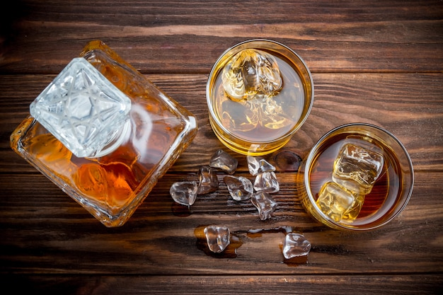 Decander and two glasses with ice and whiskey