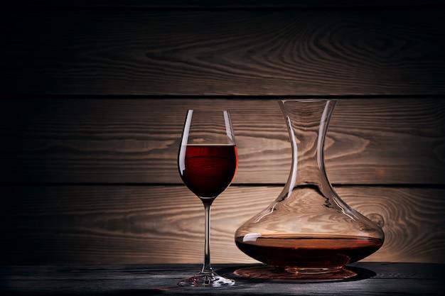 デカンターと木製のテーブルの赤ワインのガラス