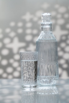 A decanter and a glass of drinking water.