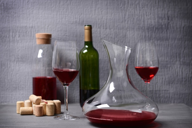 Decanter and glasses with red wine on table against gray