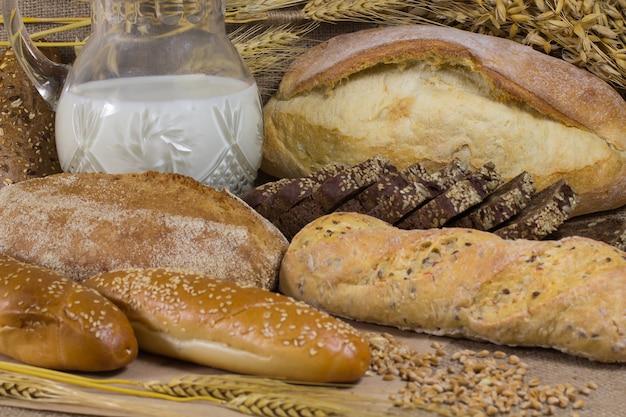 Графин молока. различные виды хлеба. ветки овса.