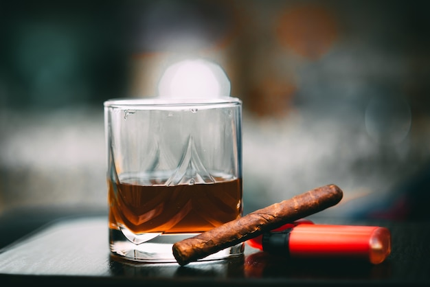 Decanter of whiskey and a glass with cuban cigar and golden lighter on a wooden table. angle view alcohol and tobacco