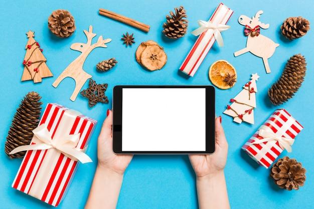 クリスマスdecationsの青い背景に彼女の手でタブレットを保持している女性の平面図です。新年の休日の概念。モックアップ