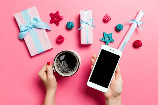 ピンクの背景に一方の手で携帯電話と別の手でコーヒーカップを保持している女性の平面図です。クリスマスdecationsとおもちゃ。新年の休日の概念。モックアップ