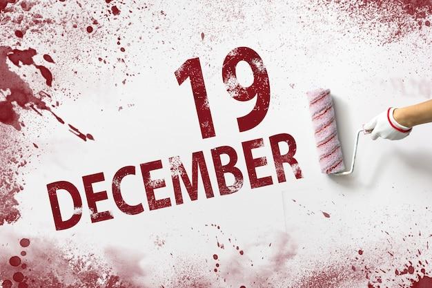 19 декабря. 19 день месяца, календарная дата. рука держит валик с красной краской и пишет календарную дату на белом фоне. зимний месяц, день года концепции.
