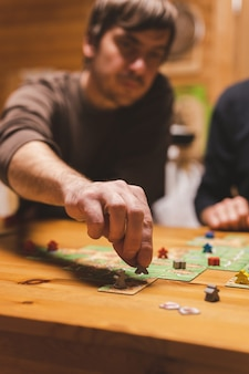 December 2020 two men friends have fun playing the carcassonne board game