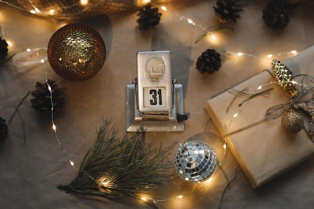 トウヒの枝と輝く花輪とクラフト紙の背景にカレンダーの12月31日