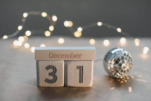 輝く花輪の背景に白い立方体のカレンダーで12月31日。クリスマス、冬、新年のコンセプト