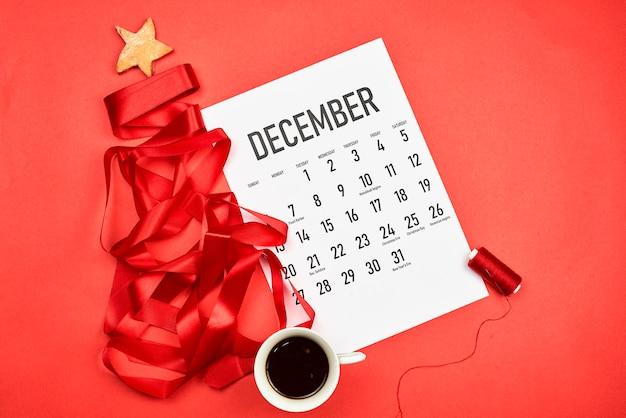 12月のカレンダーと赤いリボンで作られたクリスマスツリー