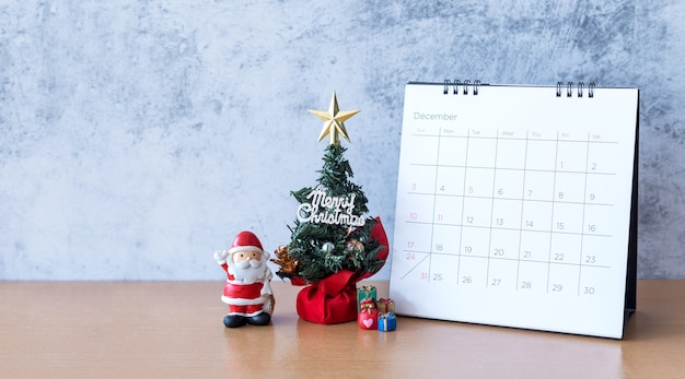 December calendar and christmas decoration - santa clause, tree and gift on wooden table. christmas and happy new year concept