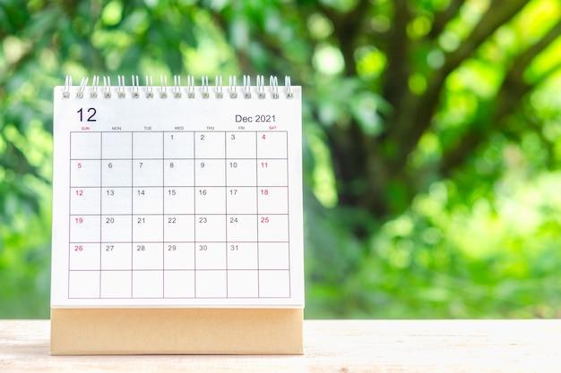 12월, 주최자를 위한 캘린더 데스크 2021은 녹색 자연 배경을 가진 나무 테이블에 대한 계획 및 알림을 제공합니다.