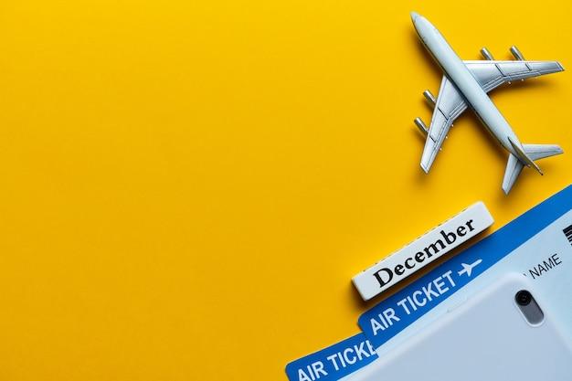 コピースペースと黄色の背景のチケットと飛行機モデルの横にある12月の休暇の概念。
