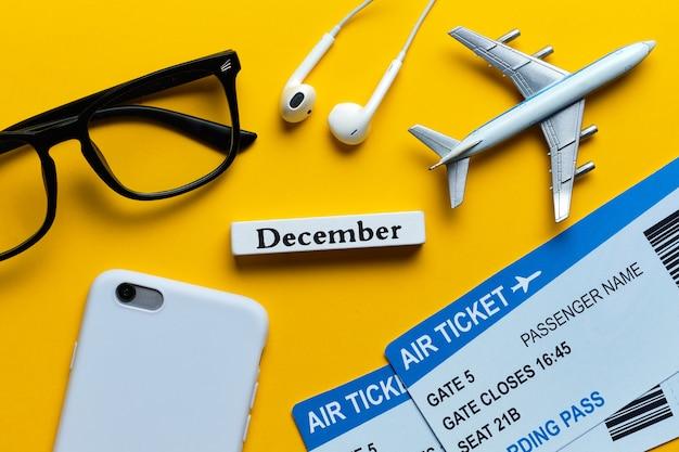 黄色の背景にチケットと飛行機モデルの横にある12月の休暇の概念。