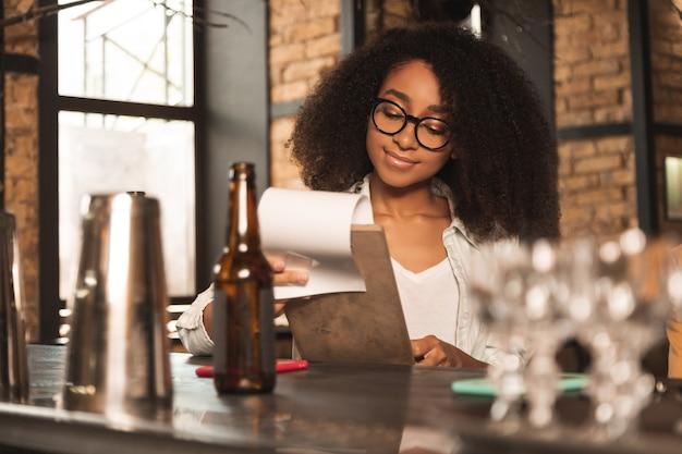まともなメニュー。バーのカウンターに座って、笑顔でパブのメニューを見て陽気な巻き毛の女性