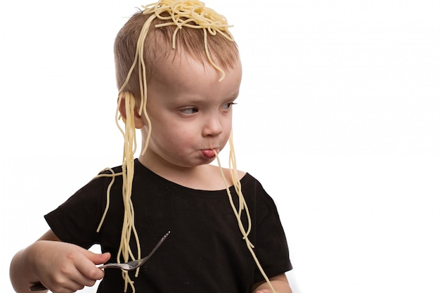 Deception, noodles on the ears. a boy in a black t-shirt is not a white isolated background. april fools day concept.