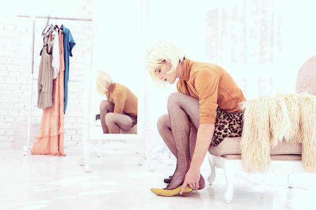 Выбор одежды. довольно блондинка странный мужчина одевается в яркую одежду, сидя на диване в спальне