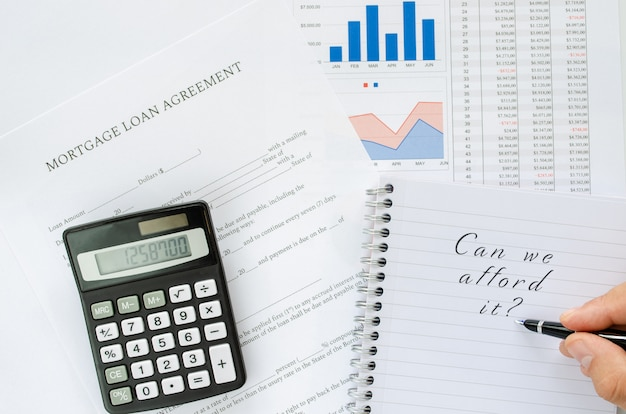 Deciding on taking a mortgage loan, concept with calculator and spreadsheets