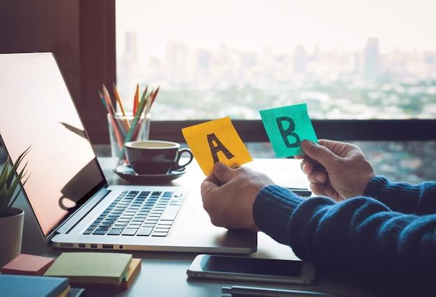 Концепции решения с бизнесменом, держащим документ a и b на столе.