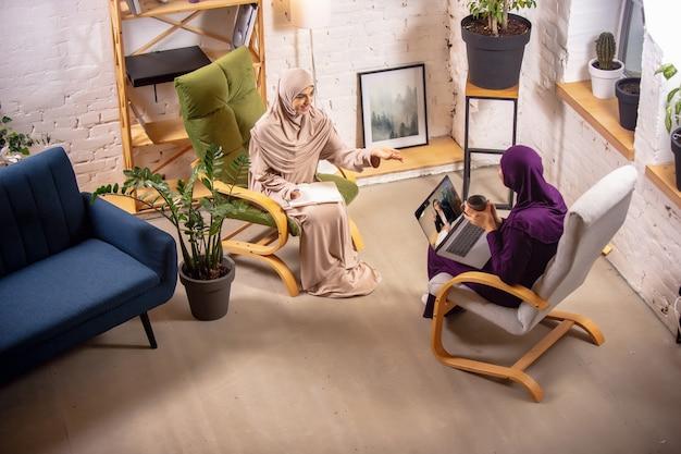 결정. 수업 중에 집에 있는 행복하고 젊은 두 명의 이슬람 여성, 안락의자, 온라인 교육. 문화, 전통, 현대인. 기기 화면을 보거나 쇼핑을 하거나 이야기를 합니다.