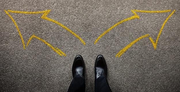 인생이나 사업 개념의 결정. 왼쪽 및 오른쪽 화살표 방향에 서있는 사업가. 평면도