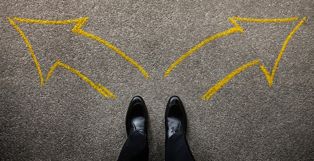 Decision in life or business concept. businessman standing on the left and right arrow direction. top view