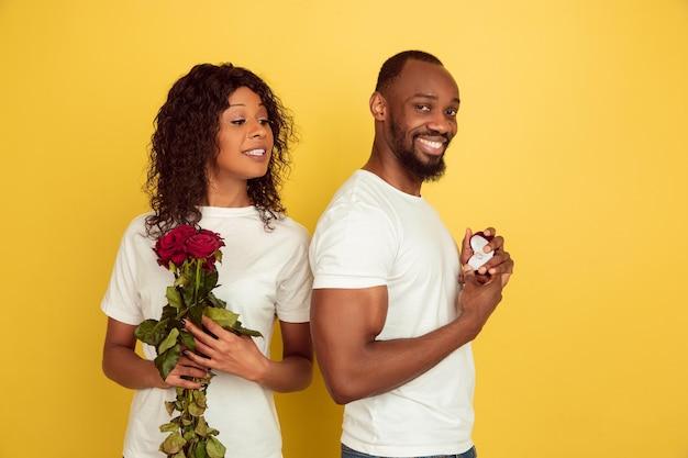 決定。バレンタインデーのお祝い、黄色のスタジオの背景に分離された幸せなアフリカ系アメリカ人のカップル。