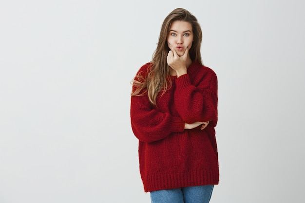 Decisions always confusing. indoor shot of charming cute female in red winter sweater squeezing lips and looking with calm and carefree expression, standing .