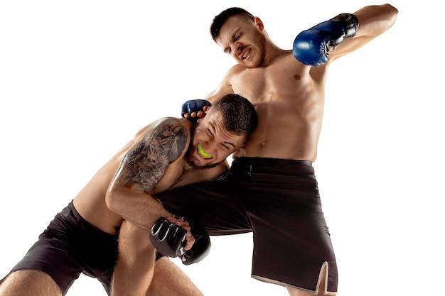 Решающий удар. два профессиональных бойца позирует на белом фоне студии. пара подходящих мускулистых кавказских спортсменов или борющихся боксеров. концепция спорта, конкуренции и человеческих эмоций.