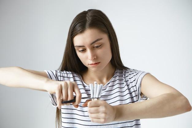 Решительная, волевая молодая темноволосая женщина, небрежно одетая, разрезает ножницами пополам связку сигарет